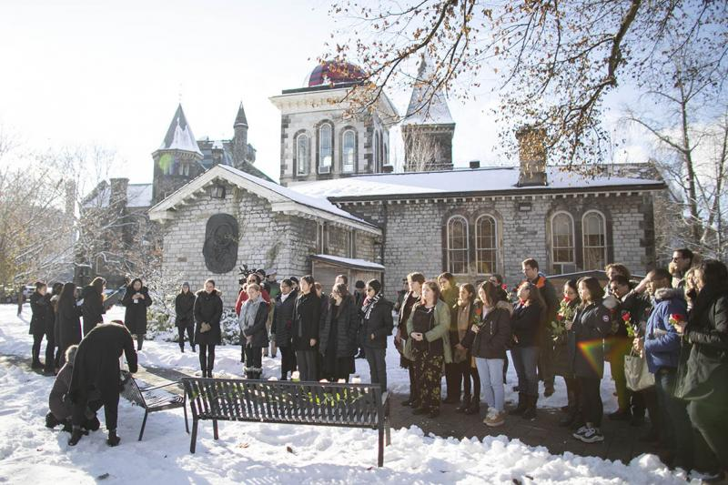 A crowd stands in the snow east of University College, watching solemnly as women place fresh roses on two metal benches.