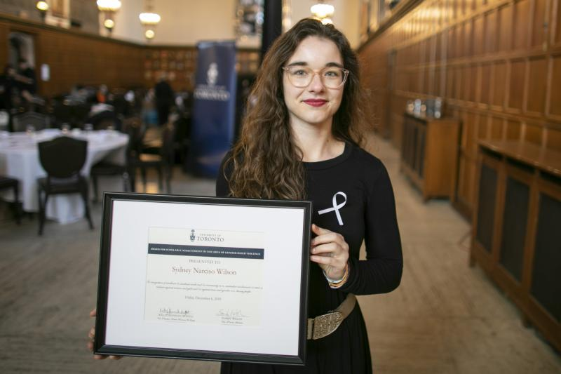 Sydney Narciso Wilson holds up a framed certificate, standing in a room in Hart House.