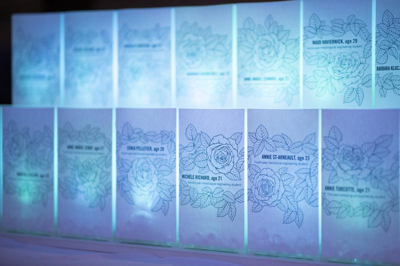 14 large cards, lit from behind, show the names and ages of the murdered women framed with a drawing of roses.