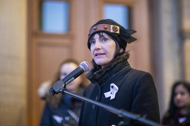 Marisa Sterling looks serious as she speaks into a microphone, wearing a white ribbon.