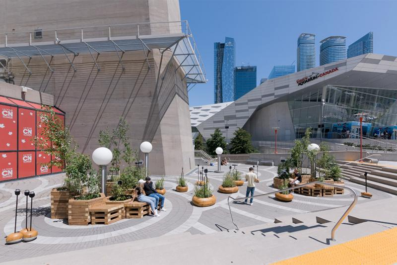 People relax on hexagonal wooden seats planted with small trees atd the base of the concrete CN Tower.