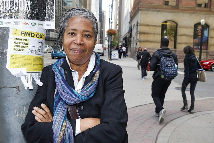 "Dionne Brand smiles as she leans, arms folded, on a telephone pole on a downtown street. The sign on the pole reads: ""How to get the job you want"""