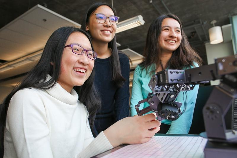 Maddy Zhang and friends laugh as they stand behind a miniature robotic arm.