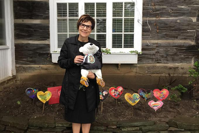 "Cindy Blackstock in front of a heart garden planted to honour the children who died in residential schools: ""I am holding Spirit Bear – the teddy bear who witnessed all the hearings of the Canadian Human Rights Tribunal on First Nations Child Welfare."""
