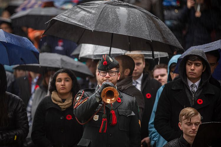 Cpl. Jonathan Elliotson plays The Last Post while attendees on the downtown Toronto campus look on (photo by Nick Iwanyshyn)