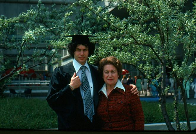 Arthur Slutsky wears an academic cap and gown and has his arm around his mother Rita, standing in a garden