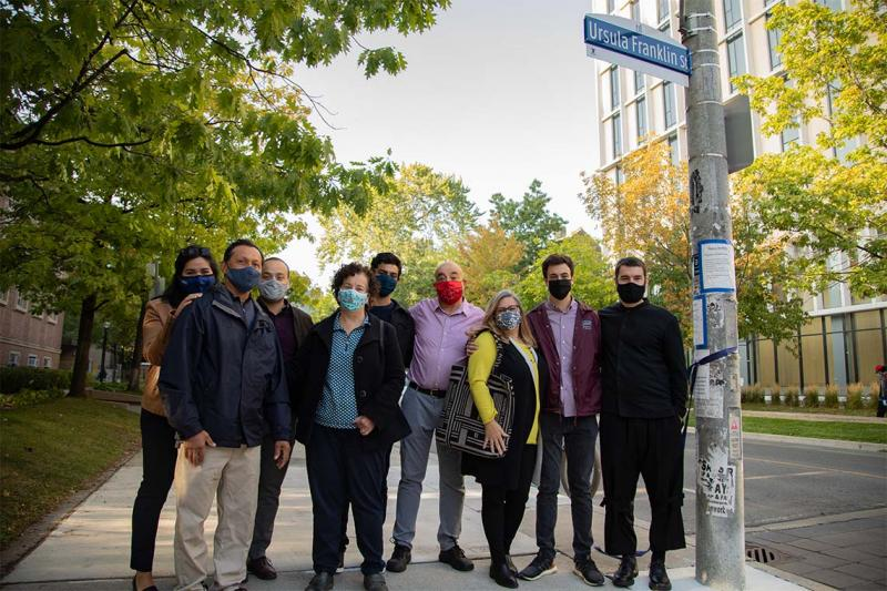 Nine Franklin family members, wearing masks, pose together under the street sign for Ursula Franklin Street.