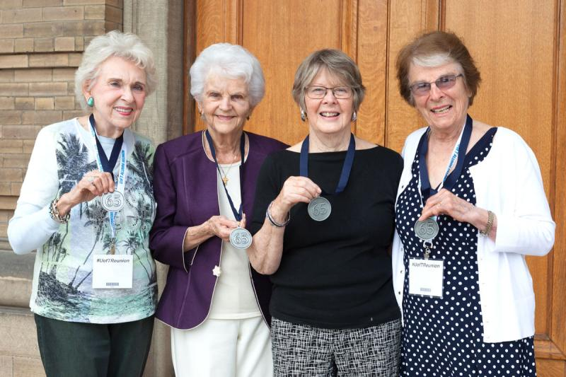 Four women hold up their 65th anniversary medals outside Convocation Hall.