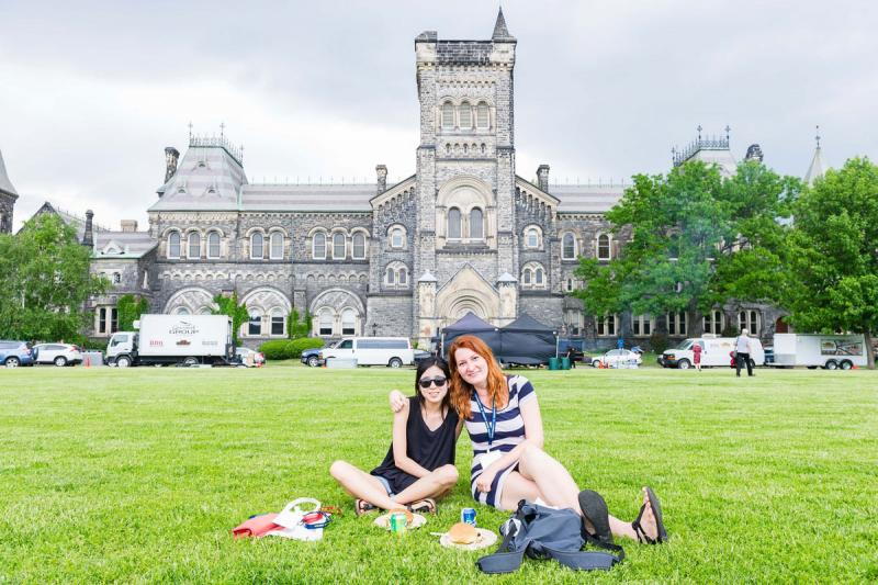 Two smiling women sit with a picnic lunch on the grass in front of University College.