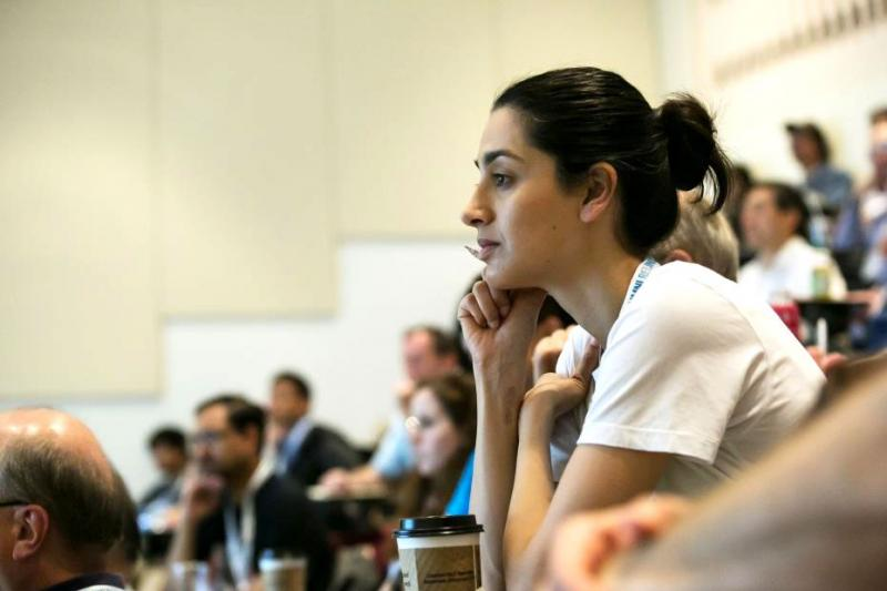 A young woman leans forward and looks intrigued while sitting in the audience in a lecture theatre.