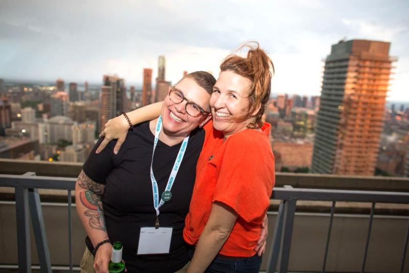 Two woman laugh with their arms around each other, standing on a balcony with a view out over Toronto.