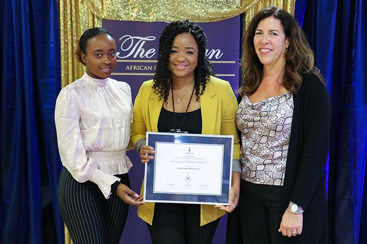 Mariam Olafuyi holds a framed certificate and smiles, flanked by Iris Hategekimana and Kelly Hannah-Moffat