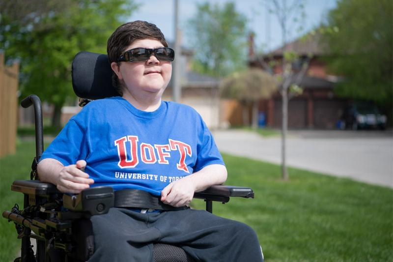 Alex Harold smiles and looks up as he sits outdoors with one hand on his wheelchair controls.