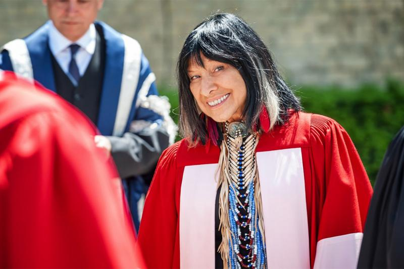 Buffy Sainte-Marie smiles while wearing academic robes.