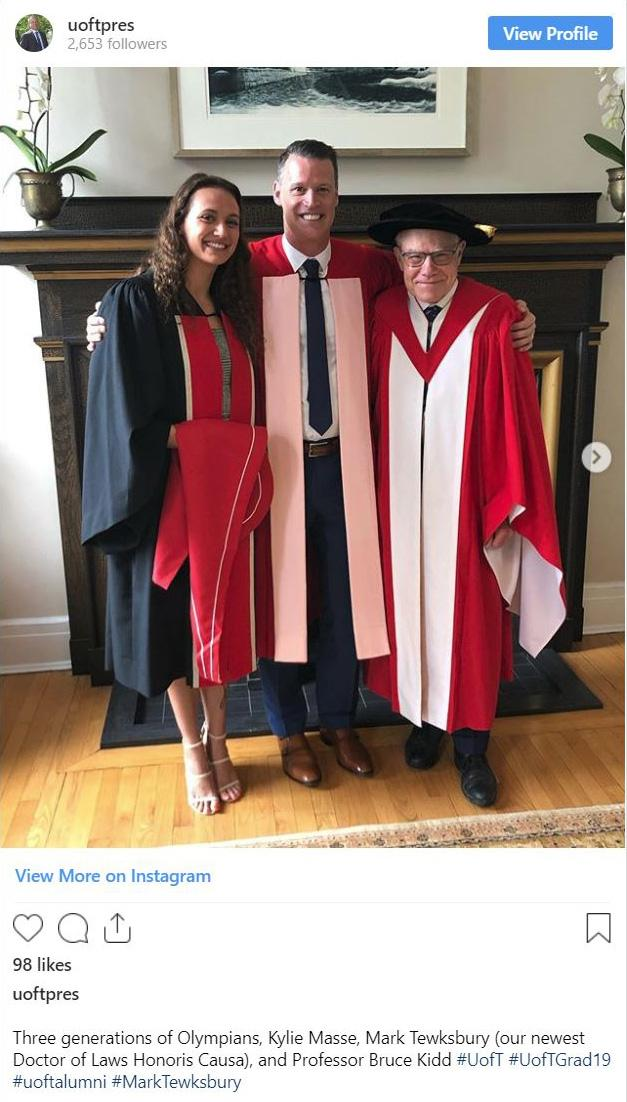 Mark Tewksbury smiles with his arms around Kylie Masse and Bruce Kidd, in front of a fireplace. All three wear academic robes.