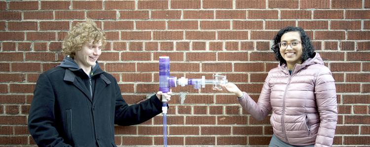 Austin Mclean and Rashmi Satharakulasinghe stand on either side of a plastic spigot which has a long spout with valves.