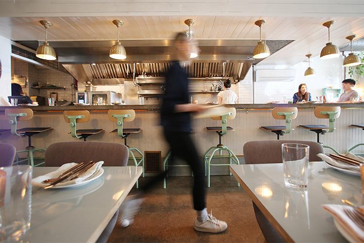 A waiter rushes past sparkling table settings at the Grey Gardens diner-style restaurant
