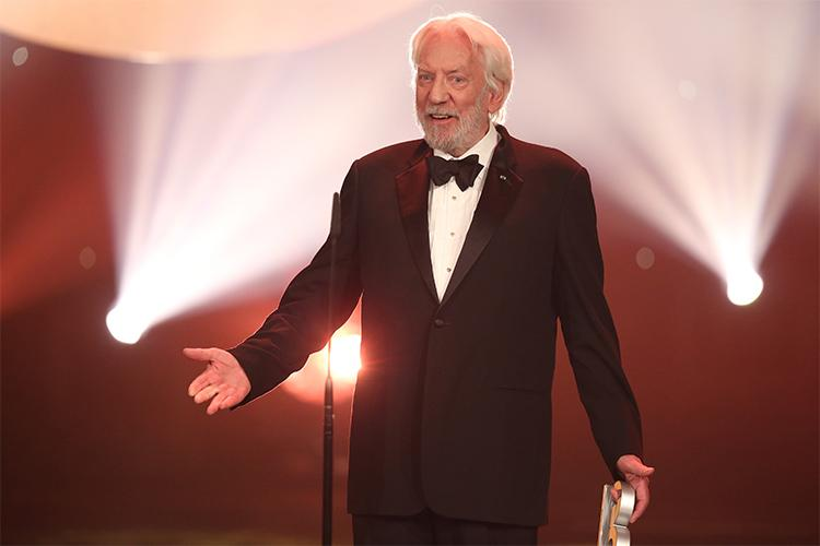 Donald Sutherland smiles and gestures, standing on a stage in spotlights while holding an award.
