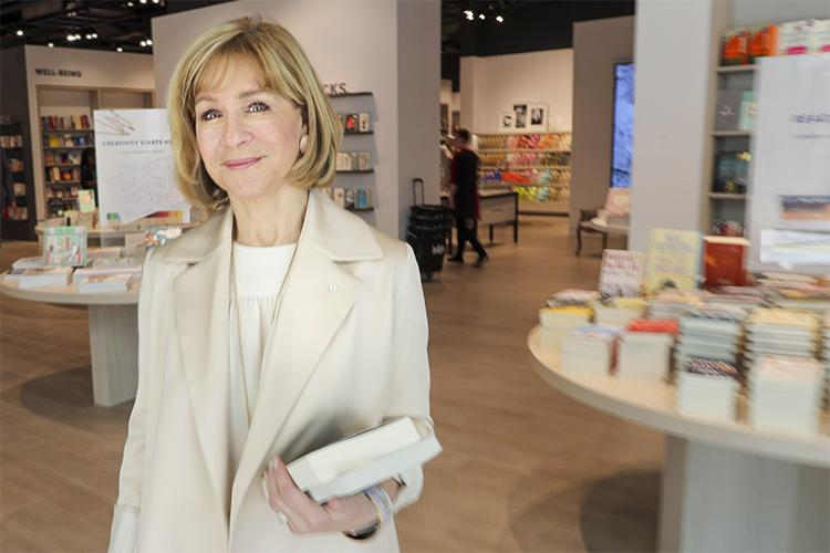 Heather Reisman smiles, holding books and standing in a bookstore.