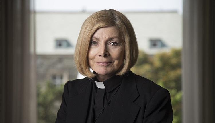 Cheri DiNovo, wearing her clerical collar, smiles while sitting by a window.