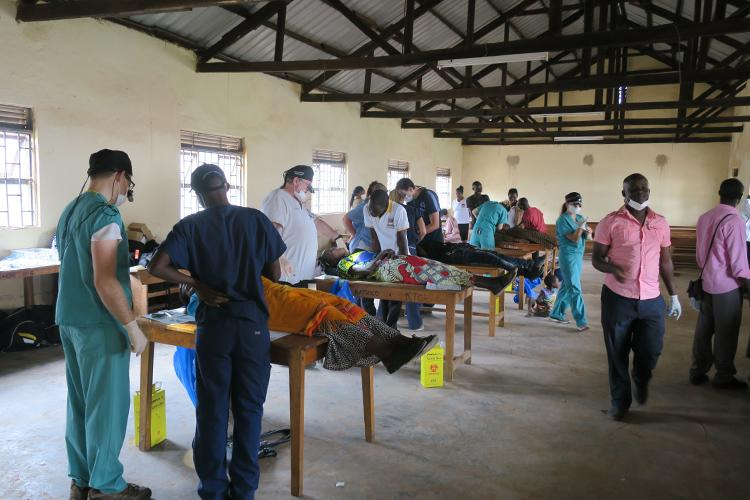 Patients in Kabale lie on tables in a large hall while volunteers in scrubs and masks examine their teeth.