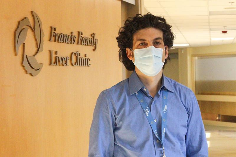 Jordan Feld, wearing a mask, stands in front of a sign that reads: Francis Family Liver Centre.