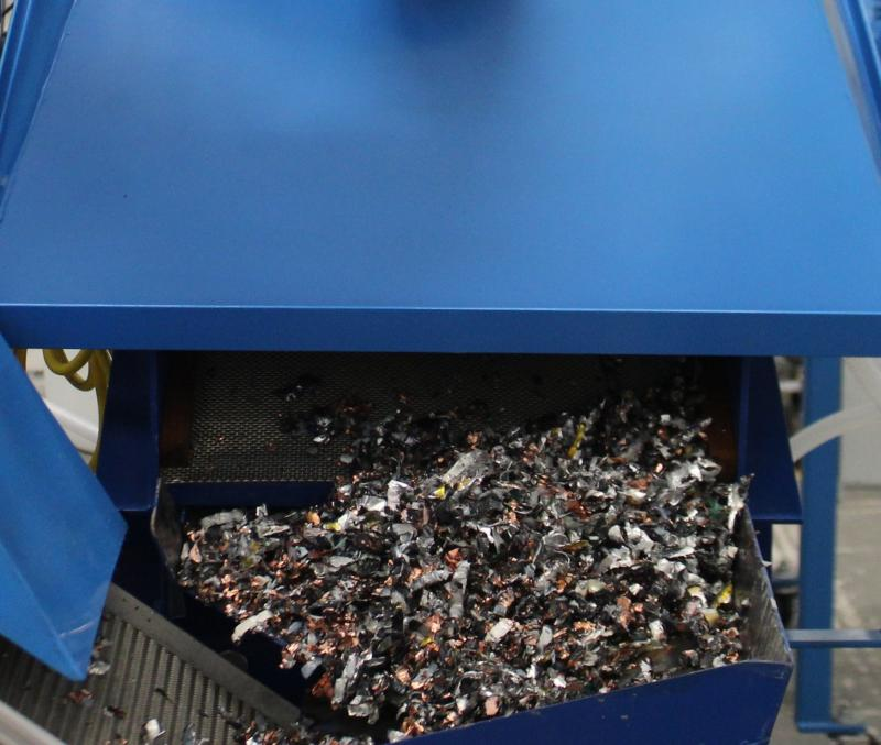 A metal container attached to a shredder is full of tiny twisted scraps of metal and plastic (photo courtesy of Li-Cycle); start-up stories