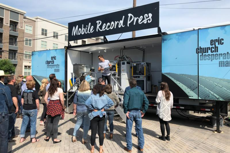 A crowd watches curiously as a man demonstrates record making on a truck bed, under a sign reading: Mobile Record Press