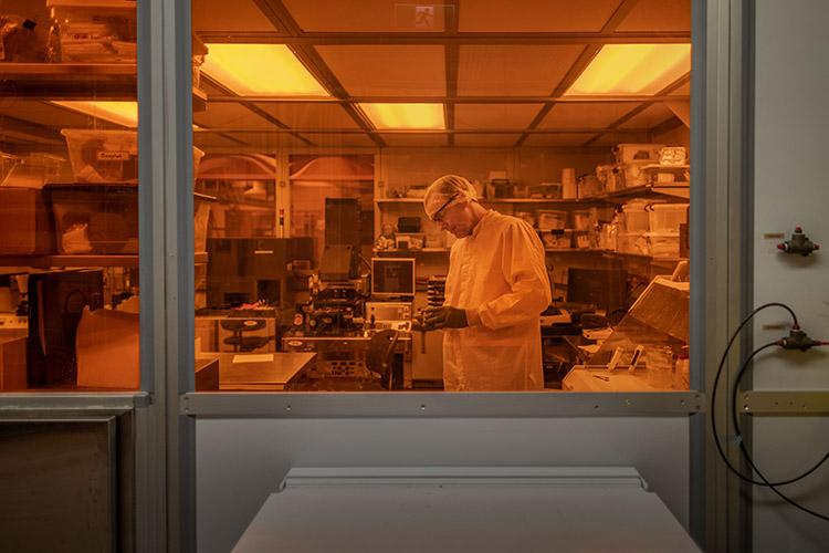 Axel Guenther, scientific director of the Centre for Microfluidic Systems, inspects microfluidic devices in a cleanroom. This fall, U of T partnered with Canada's National Research Council to create a national innovation hub focused on microfluidics (photo by Nick Iwanyshyn)