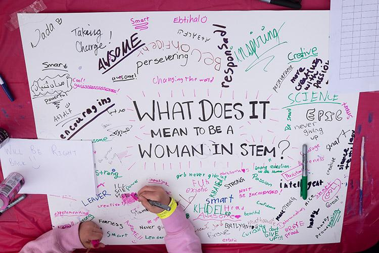 A girl adds to a poster about what it means to be a woman in science, technology, engineering and math (STEM) at Science Rendezvous on May 12 (photo by Geoffrey Vendeville).