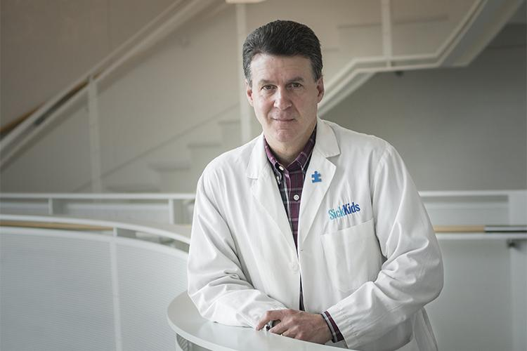 Stephen Scherer has a slight smile as he wears a SickKids lab coat and leans on a railing indoors.