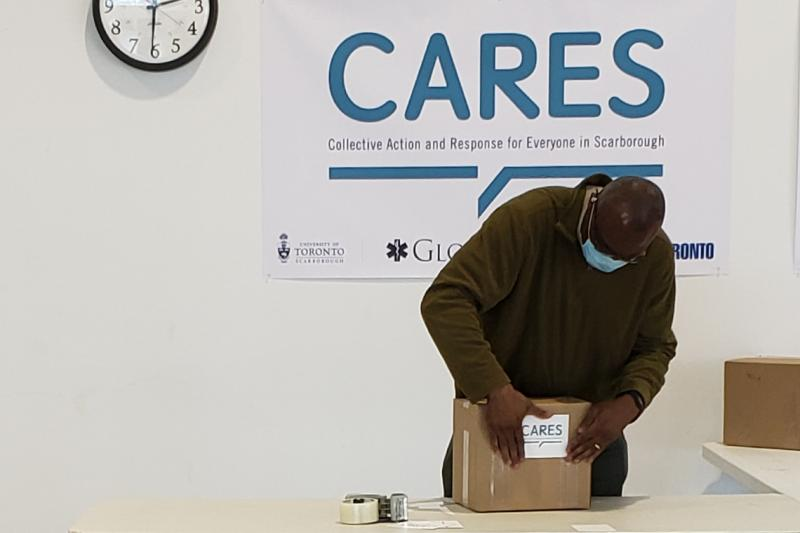 Wisdom Tettey, wearing a mask, tapes a CARES label on a cardboard box.