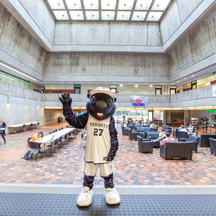 The True Blue mascot waves while standing under the skylight and concrete balconies of UTSC's Meeting Place.