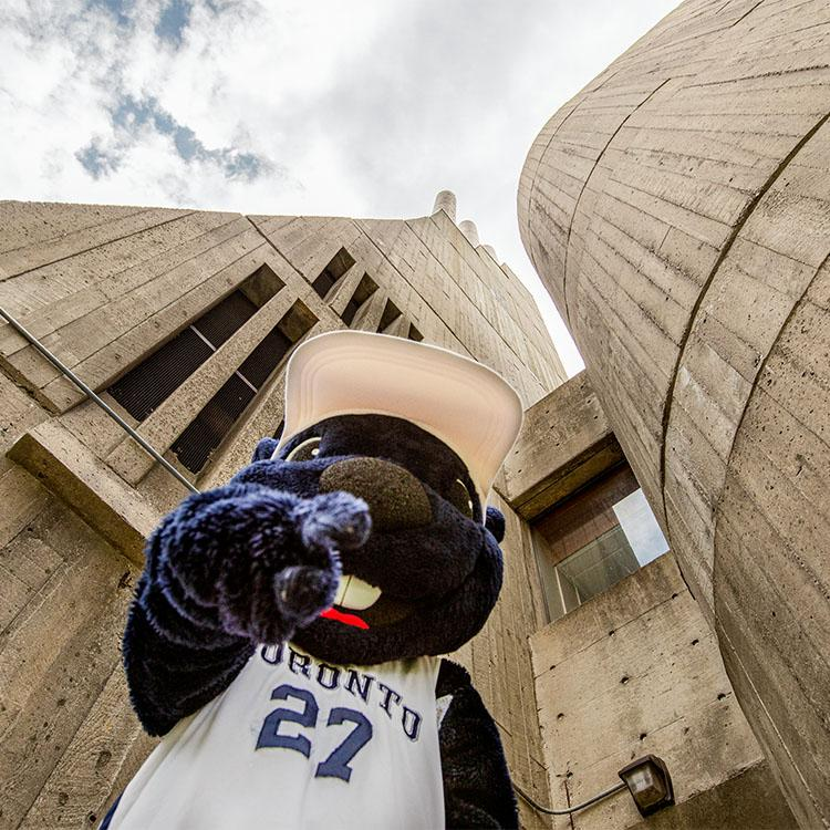 The True Blue mascot points at the camera in front of a background of a tall concrete tower topped with three smokestacks.
