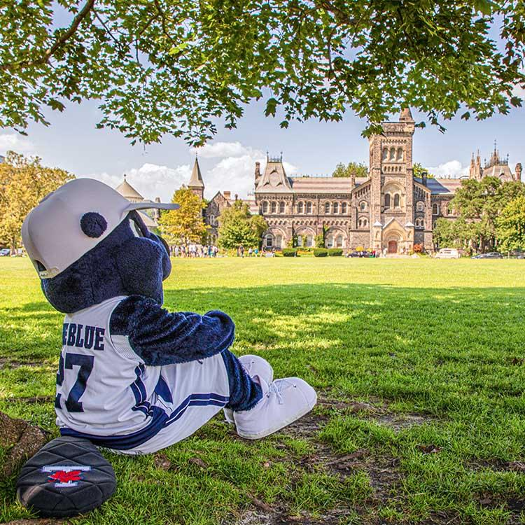 The True Blue mascot sits on the grass under a tree, arms around knees, and looks over Front Campus at University College.