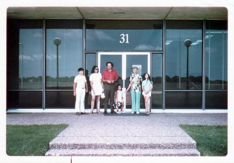A man, two women and three children stand in line in front of the glass doors of an office building.