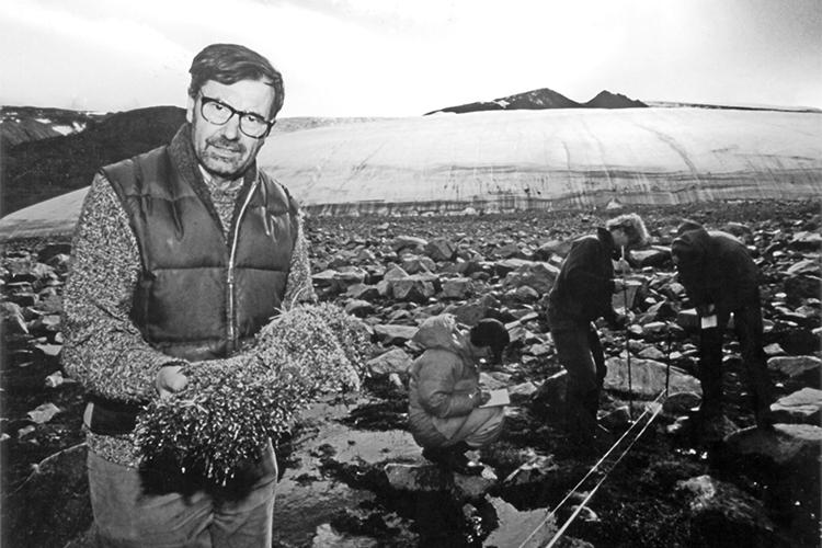 Josef Svoboda holds a clump of moss as he stands on rocks in front of a glacier.