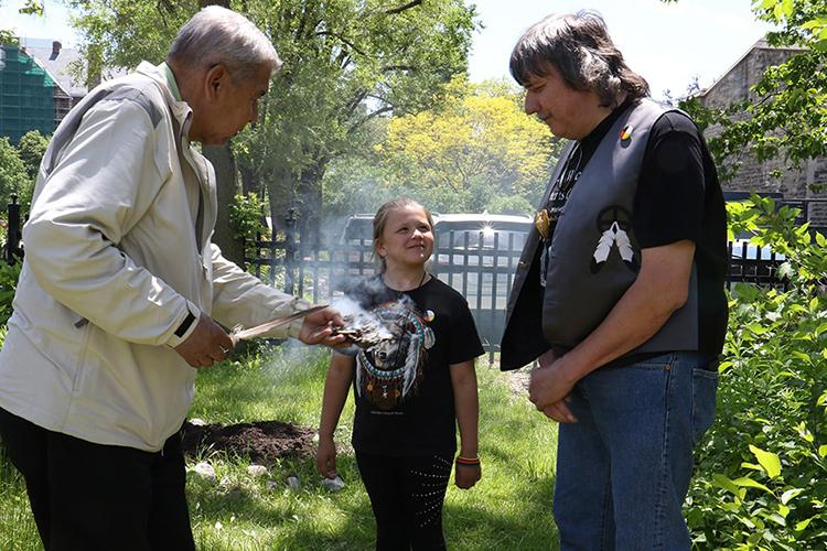 First Nations House Elder-in-Residence Andrew Wesley, Shay-Lee Strebel and Roy Strebel take part in a smudging ceremony at the opening of the garden in 2017 (photo by Hannah James)