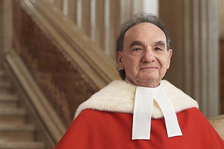 Michael Moldaver stands in front of a stone staircase, wearing his Supreme Court of Canada robes.