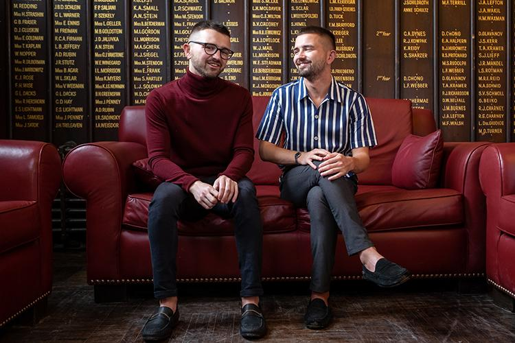 Patrick and Curtis Sobchak sitting on a large sofa in front of a wall carved with the names of U of T graduates