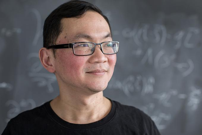 Ue Li stands in front of a blackboard and looks to his left, smiling (photo by Geoffrey Vendeville)
