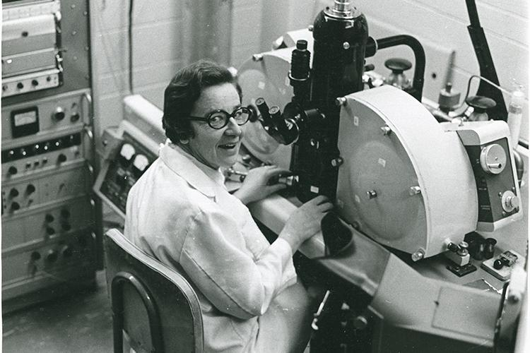 Ursula Franklin smiles in surprise as she looks up over her shoulder from her seat at a large microscope.