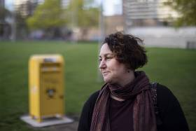 Gillian Kolla looks pensive, standing on the grass in Moss Park in front of a needle drop box.