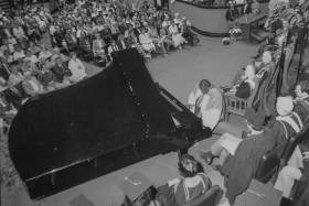 Oscar Peterson plays a grand piano on stage at Convocation Hall, surrounded by professors in academic robes.