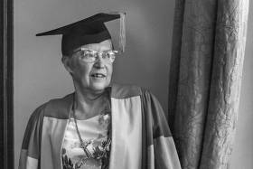 Elsie McGill smiles and looks out a window while wearing academic robes--and cat-eye glasses--in 1973.