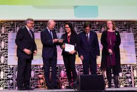 Reza Moridi, Ontario's minister of innovation, research and science, presents an award to U of T's Luna Yu (centre), the founder and CEO of Genecis EnviroTech, at this year's Discovery conference (photo by Chris Sorensen)