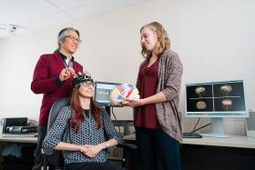 Professor Tom Chau, a University of Toronto pediatric rehabilitation engineer, works with two graduate students to develop a brain-computer interface for children (photo by Neil Ta)
