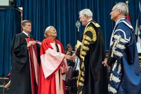 Loretta Rogers, who today received an honorary doctor of laws, honoris causa, shakes the hand of Chancellor Michael Wilson, as President Meric Gertler (right) and Toronto Mayor John Tory look on (photo by Lisa Sakulensky)