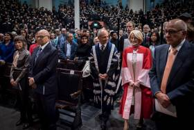 Rose Patten enters Convocation Hall with U of T President Gertler in advance of the robing ceremony. Her husband Tom Di Giacomo is second from the left (photo by Lisa Sakulensky)