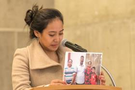 Chemi Lhamo stands at a podium, tearfully holding up a photograph of two parents with their two children. (photo by Don Campbell)